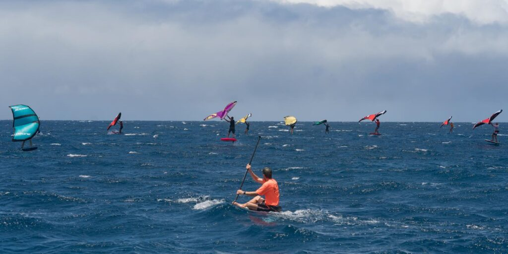 The wing surfers race other craft in the Paddle Imua event